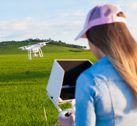 the sun and shade: Young woman holding radio controller with tablet and sun shade flying drone uav over a field. Aerial video and photography maker. Hovering aircraft in the background. Stock Photo