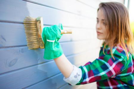 若い女性が木造舌と溝クラッド標高壁保護ニスや塗料を適用します。住宅改善 diy コンセプト。