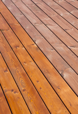 deck: Patio wooden deck floor freshly stained with wood oil. Before and after varnishing effect. Home improvement concept. Stock Photo