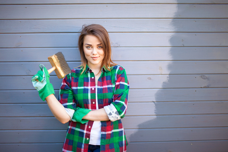 Young working woman with paint brush, freshly painted wooden exterior wall behind her, handy woman concept Stock Photo