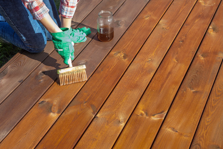 Woman applying protective varnish or wood oil on a patio wooden floor, house maintenance concept. Before and after effect Stok Fotoğraf