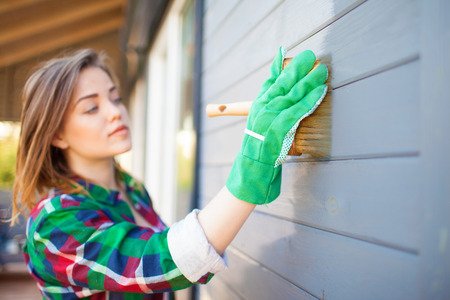 Woman applying protective varnish or paint on wooden house tongue and groove cladding elevation wall. Focus on hand with brush. House improvement diy concept.
