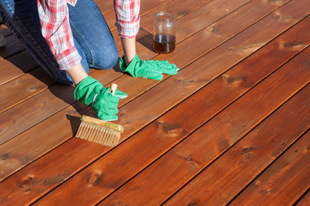 hardwood floor: Woman applying protective varnish or wood oil on a patio wooden floor, house maintenance concept. Before and after effect Stock Photo