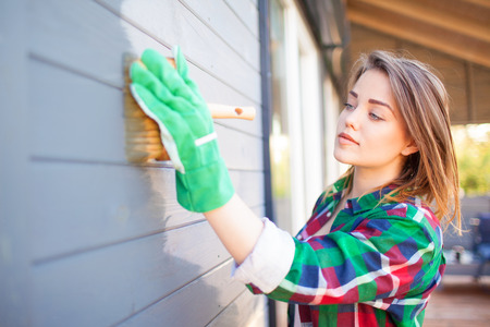 Young woman applying protective varnish or paint on wooden house tongue and groove cladding elevation wall. House improvement diy concept. Stockfoto