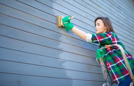 Jonge vrouw die beschermende lak of verf op houten huis messing en groef gevelbekleding hoogte muur. Huis verbetering diy concept.