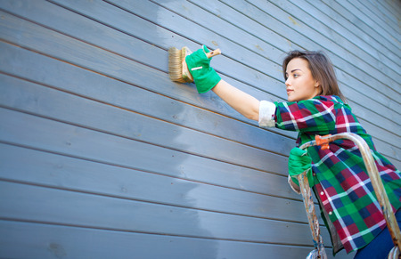 Young woman applying protective varnish or paint on wooden house tongue and groove cladding elevation wall. House improvement diy concept. Foto de archivo