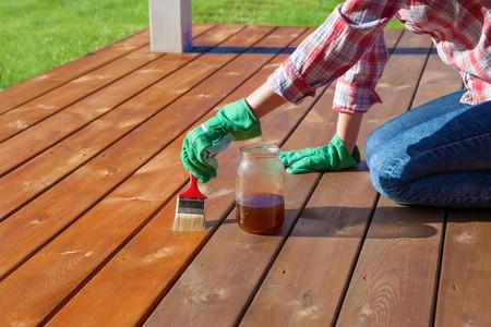 Vrouw die beschermende vernis of hout olie op een terras houten vloer, huis onderhoud concept. Voor en na effect