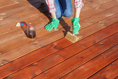 home exterior: Woman applying protective varnish or wood oil on a patio wooden floor, house maintenance concept. Before and after effect Stock Photo