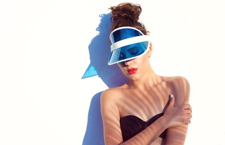 비키니 선 바이저를 착용하는 아름 다운 젊은 여자의 여름 해변 스타일 초상화. 패션 뷰티와 메이크업 화장품 개념