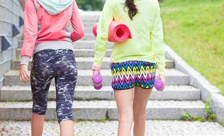 young friends: Two fit young women friends holding fitness mat and weights walking up stairs in a park, outdoor workout concept