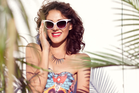 Summer style portrait of young happy smiling attractive woman wearing sunglasses. Tropical summer holiday fashion beauty concept