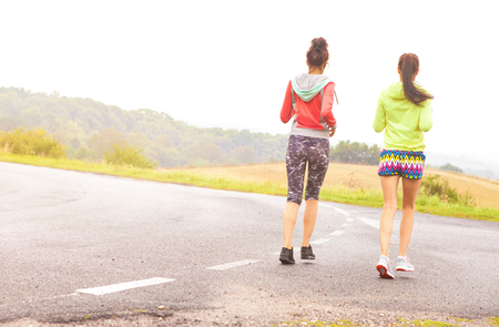 mujeres corriendo: Two fit young women friends running on the road. Active healthy lifestyle and outdoor workout concept