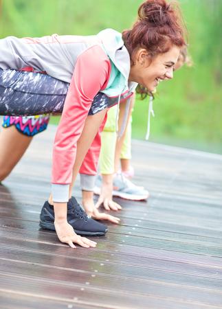 Gli atleti felici delle donne degli amici alla linea di partenza di sprint che si preparano per correre. Esercizi all'aperto, competizione di amicizia e concetto di stile di vita attivo. Archivio Fotografico