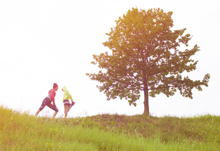 concep: Two fit young women friends exercising on the hill. Active healthy lifestyle and outdoor workout concep Stock Photo