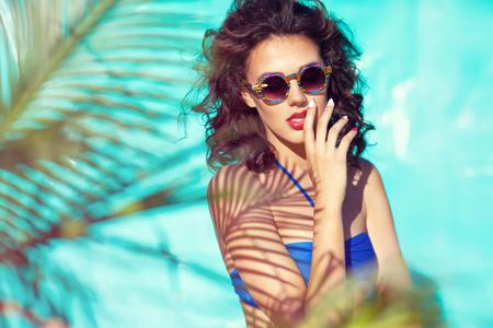 fashion and beauty: Summer beach style portrait a beautiful young woman wearing bikini and sunglasses under a palm tree