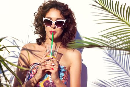 물을 마시는 젊은 매력적인 여자 선글라스를 착용하는 여름 스타일의 초상화입니다. 열대 여름 휴가 패션 뷰티 개념