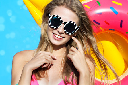 floats: Summer beach style portrait a beautiful smiling happy young blonde woman wearing bikini and sunglasses with inflatable swimming pool toys Stock Photo