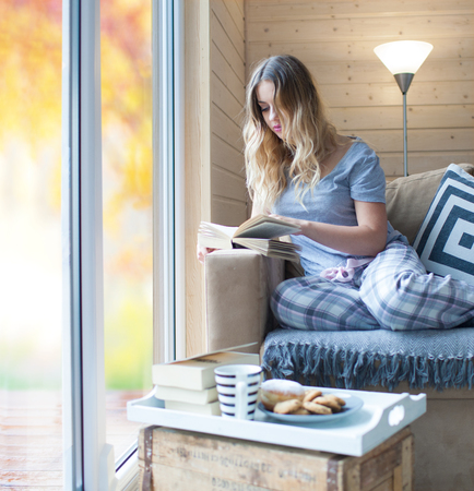 cozy: Young beautiful blonde woman with cup of coffee sitting home relaxing by the window reading book wearing pajamas. Blurred garden fall background. Lazy day off concept.