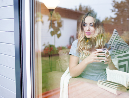 Young beautiful blonde smiling woman with cup of coffee sitting on a home couch by the window. Backyard reflection on the glass Stok Fotoğraf