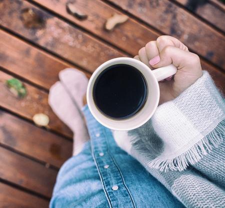 Schließen Sie herauf Ansicht von oben genanntem der Frau, die in der Decke umfasst wird, die einen Tasse Kaffee hält. Holzterrassendeck mit Fallblättern als der Hintergrund Standard-Bild - 74464424