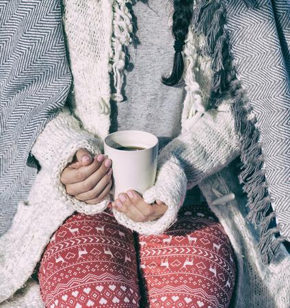 Cerca de la mujer cubierta en suéter y retención manta taza de café. Concepto de invierno de Navidad.
