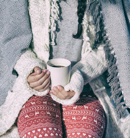 christmas winter: Close up of woman covered in sweater and blanket holding cup of coffee. Christmas winter concept.