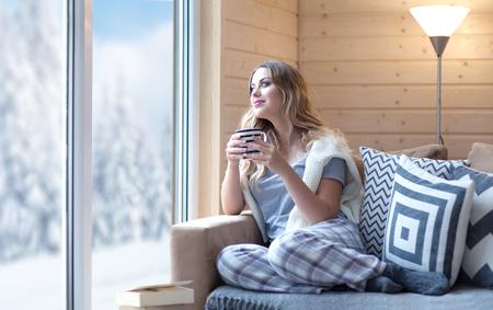 Jonge mooie blonde vrouw met een kopje koffie zitten thuis in de woonkamer door het raam. Winter sneeuw landschap te bekijken. Luie dag uit-concept