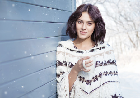 beautiful weather: Beautiful natural young brunette woman with cup of coffee, wearing knitted poncho, standing at the house. Winter snowing weather and woods landscape in the background Stock Photo