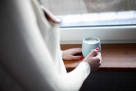Junge Brunettefrau mit dem Tasse Kaffee, der das Fenster, Winterlandschaft draußen bereitsteht Standard-Bild - 74620190