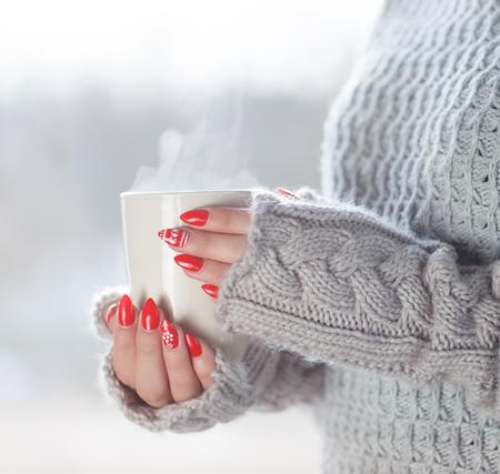 Frau trägt gestrickte Pullover und Handschuhe mit einer Tasse heißer Dämpfe Kaffee, humorvoll Haus Heizenergieeinsparung halten Standard-Bild - 74620191