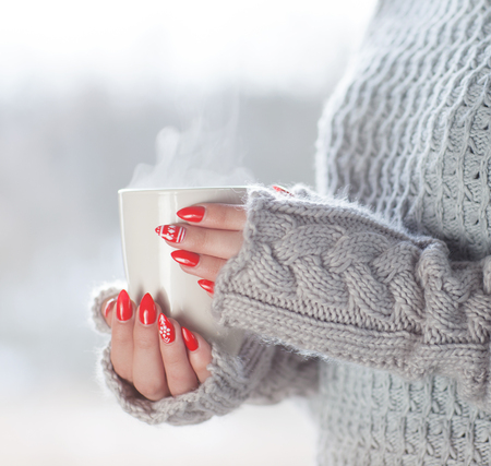 hot drink: Woman wearing knitted sweater and gloves holding a cup of hot steaming coffee, humorous home heating energy saving