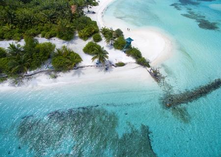 Zwei kleine Leute, die am weißen Sandstrand stehen. Landschaftsmeerblickvogelperspektive über Malediven Male Atoll Island. Strand mit dem Leibwächterkontrollturm von oben gesehen. Standard-Bild - 76879503