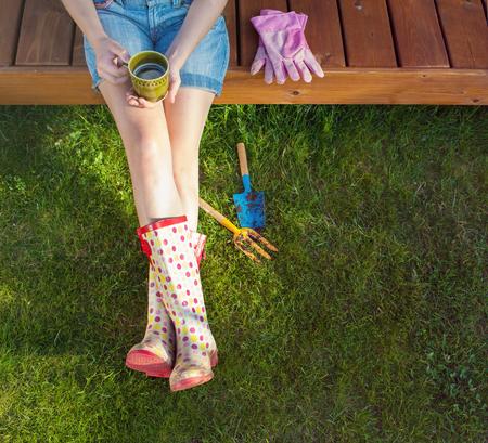 Frau mit dem Tasse Kaffee, der auf einer hölzernen Patioplattform tragenden Wellington-Stiefeln stillstehen nach der Arbeit im Garten sitzt Standard-Bild - 74620192