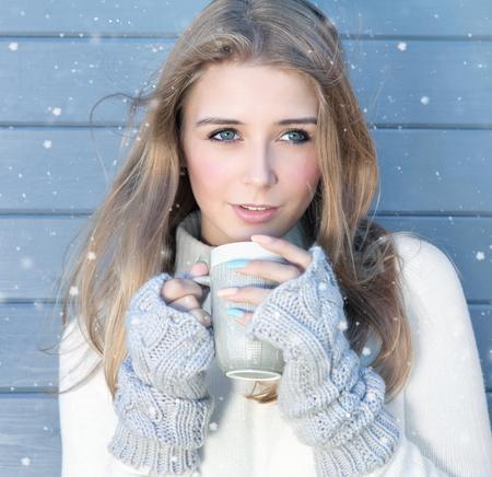 Schöne natürliche junge Blondine, die gestrickte Strickjacken- und Handschuhtrinkbecher Kaffee im Freien tragen. Schneiendes Schneewinterkonzept. Standard-Bild - 74409387