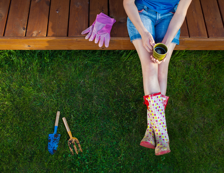 Frau mit Tasse Kaffee sitzt auf einem hölzernen Terrassendeck nach der Arbeit im Garten Standard-Bild - 74620197