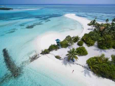 Kleine Frau, die sich am weißen sandigen Strand mit dem Leibwächterturm gesehen von oben hinlegt. Landschaftsmeervogelperspektive über der Malediven-männlichen Atollinsel. Standard-Bild - 76879949