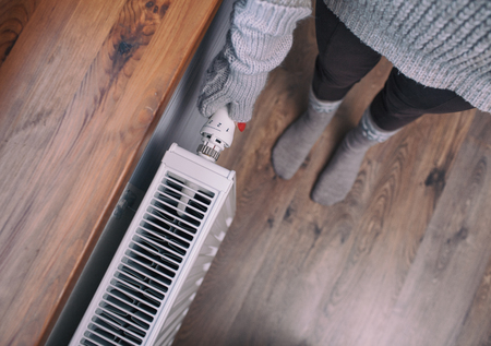 regulating: Close up of woman wearing woolen gloves hands turning up heater. Snow at the windowsill. Winter energy saving concept. Stock Photo