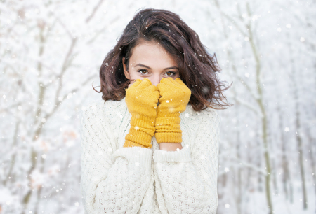 아름 다운 자연 젊은 미소 갈색 머리 여자 짠된 스웨터와 장갑 숲에서. 눈이 눈이 겨울 개념을 눈.