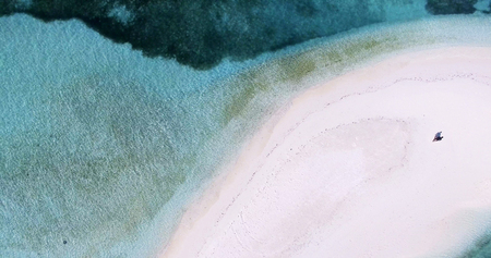 cenital: Panoramic landscape seascape aerial view over the Maldives Male Atoll island shore. Man standing on the white sandy beach seen from above.
