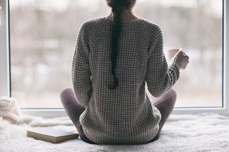 Durchdachte junge Brunettefrau mit dem Buch und Tasse Kaffee, die durch das Fenster, undeutliche Winter forrest Landschaft draußen schauen Standard-Bild - 74620188
