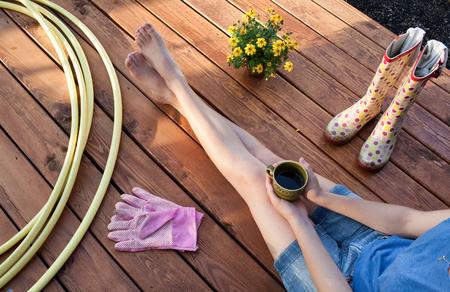 Frau mit dem Tasse Kaffee, der auf einer hölzernen Patioplattform stillsteht nach dem Arbeiten im Garten sitzt Standard-Bild - 74464711