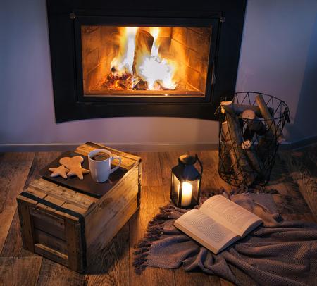 Leuchten verzierten Kamin, Laterne, Kaffee, Süßigkeiten und ein Buch. Winterweihnachts entspannen Ferienhaus-Konzept. Standard-Bild - 74856242
