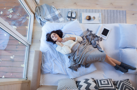 Young beautiful brunette woman lying down on the bed by the window. Top view from above. Lazy day off concept