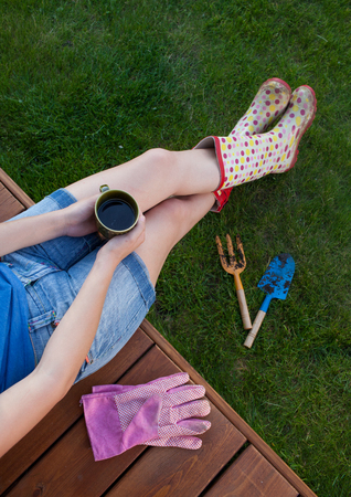 porches: Woman with cup of coffee sitting on a patio wooden deck resting after working in the garden