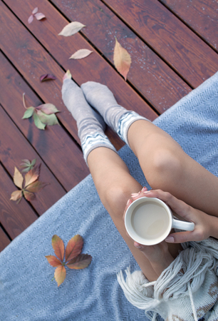 Woman with cup of coffee sitting relaxing on patio wooden deck, she's covered in a blanket. Fall leaves on wooden patio deck. Autumn concept. photo
