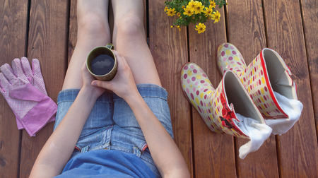 Woman with cup of coffee sitting on a patio wooden deck resting after working in the garden