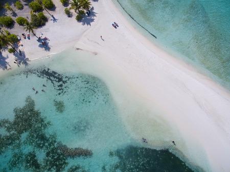 Landschaft Seelandschaft Luftaufnahme über eine Insel Malediven Male Atoll. Weißer Sandstrand und kleine Leute von oben gesehen Standard-Bild - 74620208