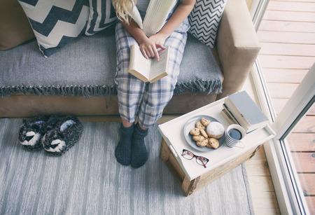 Schließen Sie oben von der Frau, die auf einer Couch sitzt, die ein Buch hält. Auszeit oder Student Home Education-Konzept. Standard-Bild - 75779854