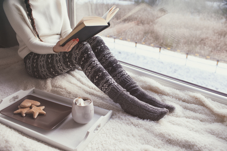 Young woman with cup of coffee and gingerbread is reading a book sitting home relaxing by the window. Snow winter home chill out concept.