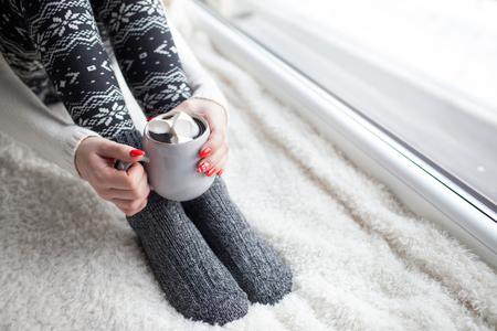 Close up der Frau Füße und Hände, die eine Tasse Kaffee mit Marshmallows zu halten. Nordic Druck Winter Nageldesign Standard-Bild - 74409378